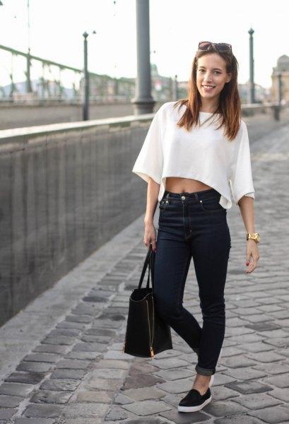 vit, vidsträckt tröja med vida ärmar och svarta jeans med muddar