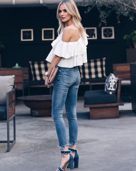 En rufsig axelblus med korta skinny jeans och jeansklackar