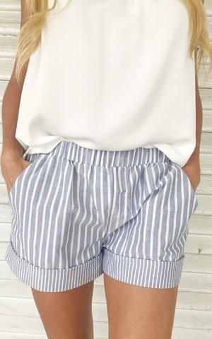 vit ärmlös topp med en avslappnad passform och grå randiga minishorts med elastisk midja