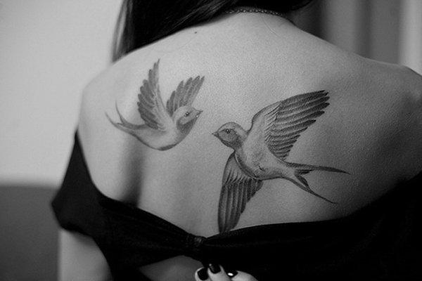 två flygande duvor uppe i ryggen