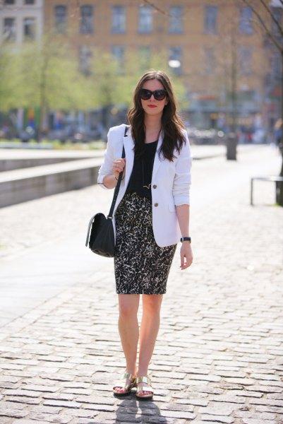 vit kavaj med svart blus och figurkramande kjol med hög midja