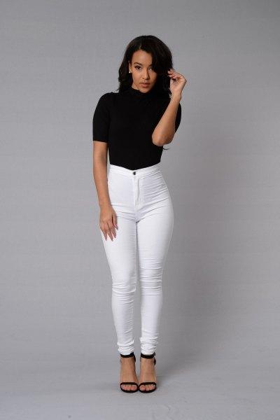 svart kortärmad mock-hals topp med vita skinny jeans med hög midja