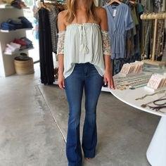 vit blus veckad från axeln med utsvängda blå jeans