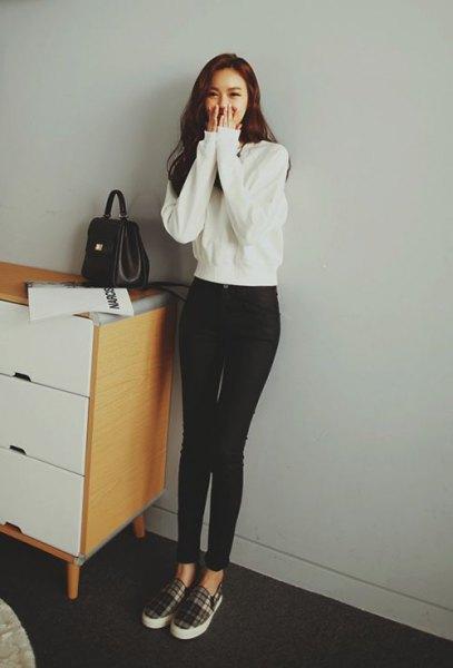 vit tröja med svarta smala jeans med hög midja och rutiga canvasskor