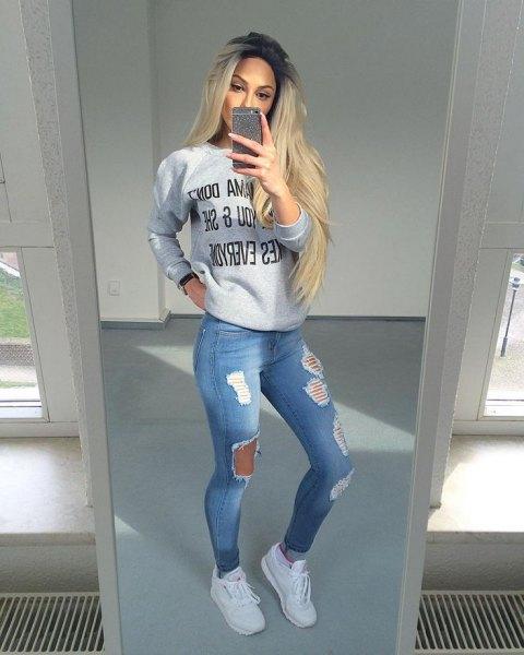 grå grafisk tröja med ljusblå jeans