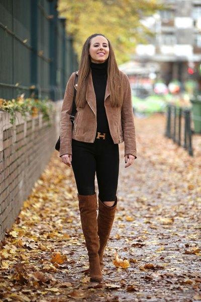 brun matt läderjacka med svarta jeans och höga kamelstövlar