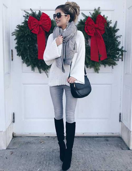 vit, grovstickad tröja med grå skinny jeans och svarta, knähöga, höga stövlar