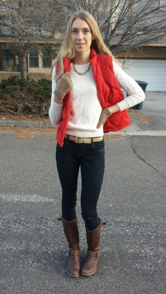 röd väst med vit stickad tröja med rund halsringning och svarta skinny jeans