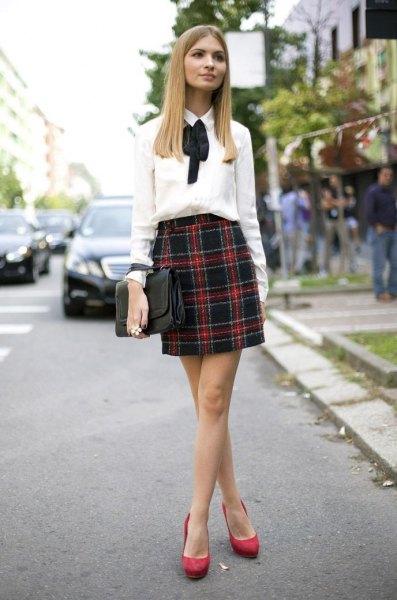 vit rosettskjorta med rosett och mörkblå och röd minikjol