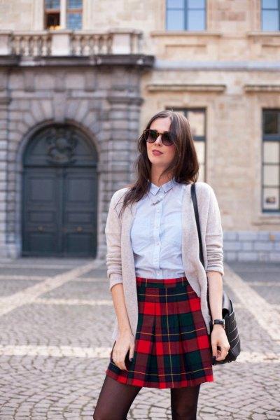 ljusblå skjorta med knappar, grå kofta och svart rutig minikjol