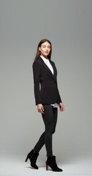 vit skjorta med knappar, svart kavaj och ankelstövlar med klackar