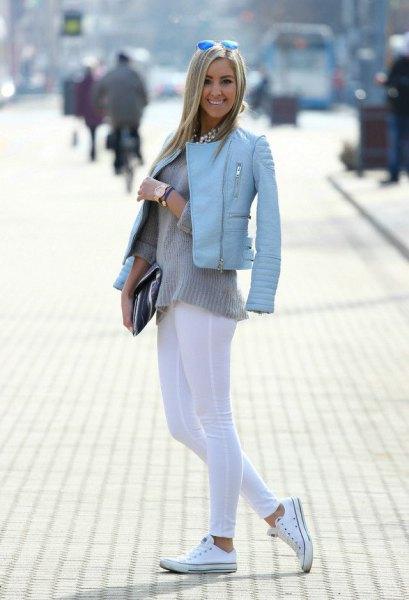 ljusblå skinnjacka med vita leggings och canvasskor