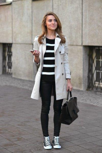 ljusgrå långlinnekappa med svartvitt randig tunikatröja och jeans
