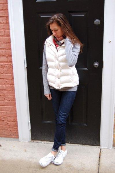 vit pufferväst med grå långärmad T-shirt och mörkblå jeans med muddar