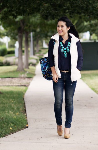 vit pufferväst med skjorta med knappar och mörkblå skinny jeans