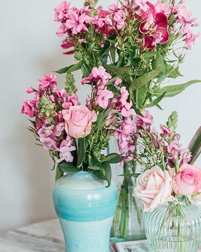 Tre vaser med olika höjd fyllda med felaktiga rosa blommor.