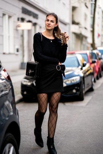 Använd en svart kjol med en svart stickad tröja