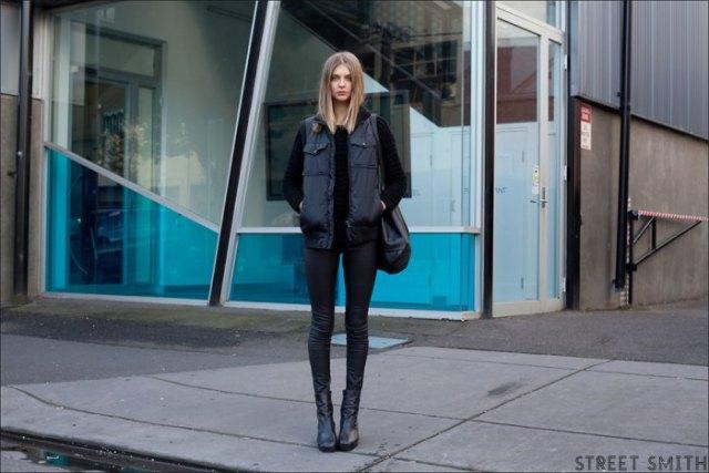 svart lång dunväst med tröja och smala jeans