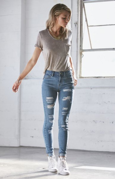 grå t-shirt rippade blå skinny jeans