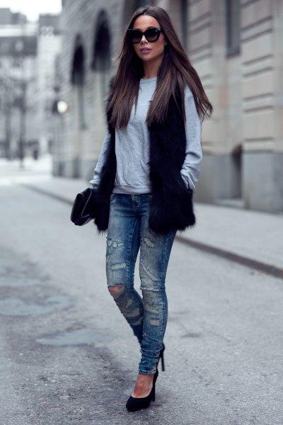 svart fuskpälsväst med grå tröja och slitna slim fit-jeans
