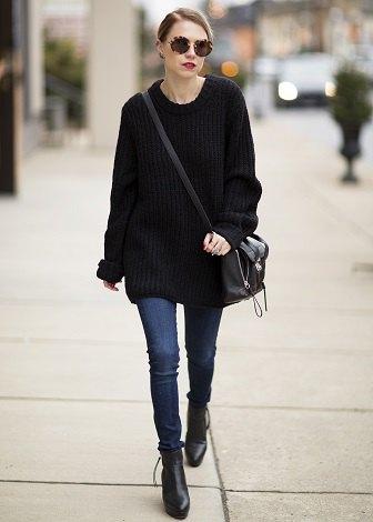 svart överdimensionerad tröja med blå smala jeans och läderstövlar