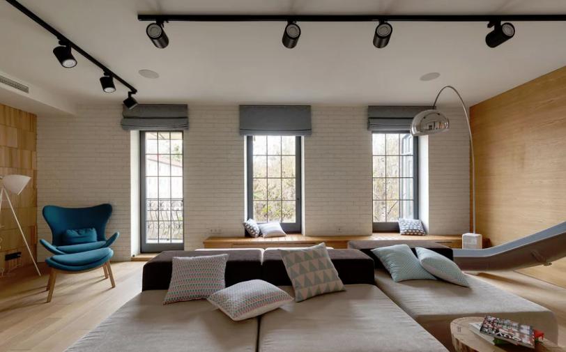 Vardagsrummet är ett stort öppet utrymme med höga fönster, flera.