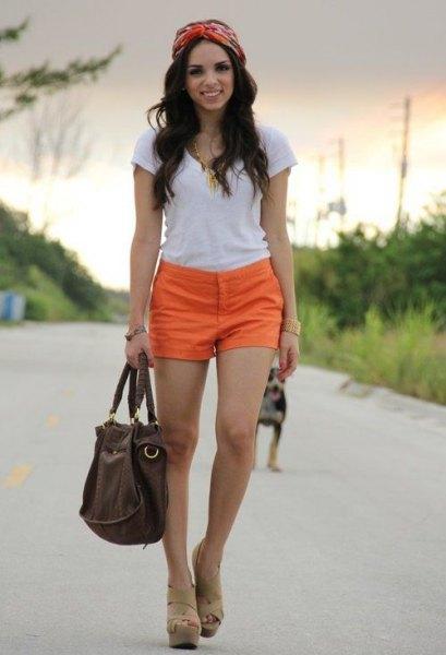 vit t-shirt med orange shorts och kala sandaler
