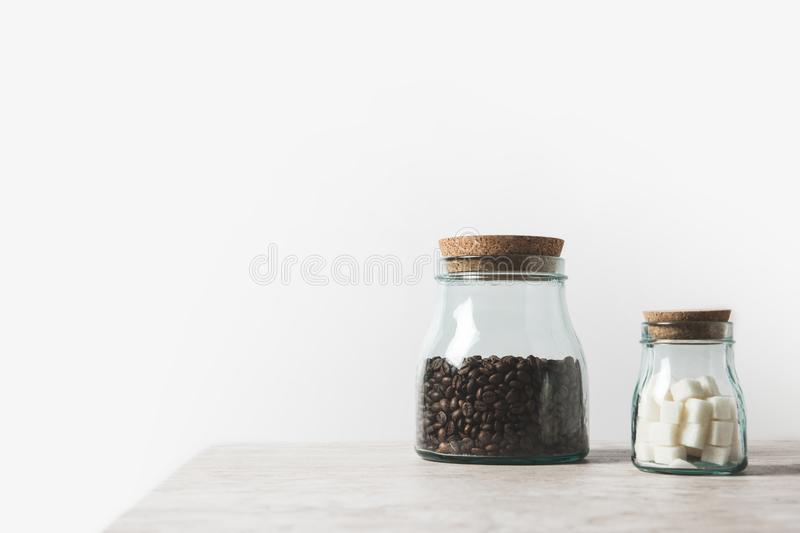 Kaffebönor och raffinerat socker i glasflaskor på marmorbordet.
