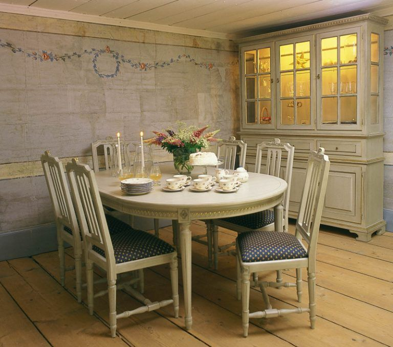 Fredlig matsal med bondgårdsmöbler och industriljus